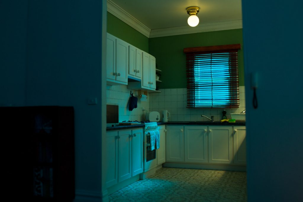 A miniature suburban kitchen at night, lit with green and blue tones. Eerie, empty.