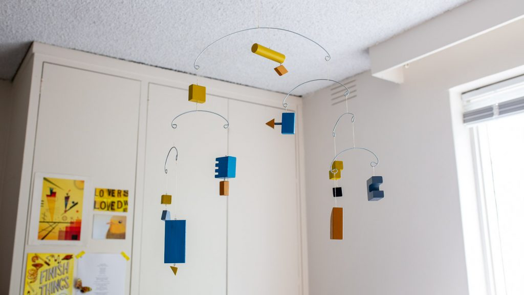A kinetic hanging mobile made of coloured wooden blocks.