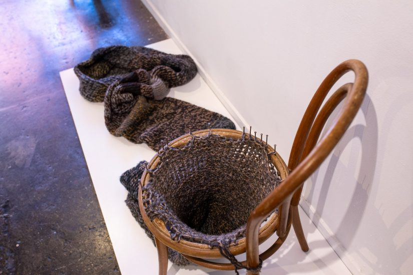 A sculpture where a Bentwood chair has been turned into a circular loom, with a dark knitted tube emerging from the bottom.