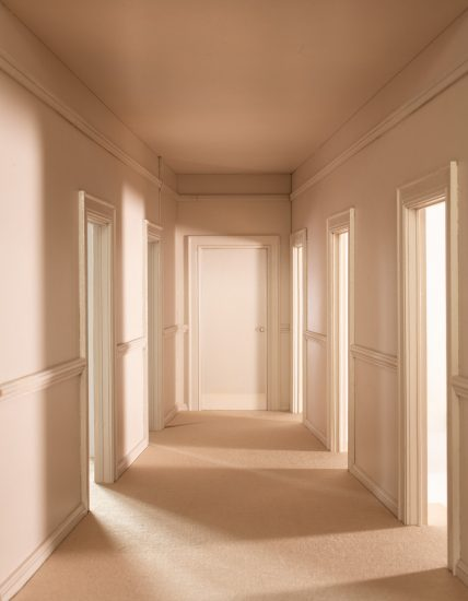 A scale model of an eerily empty hallway with open doorways on either side.