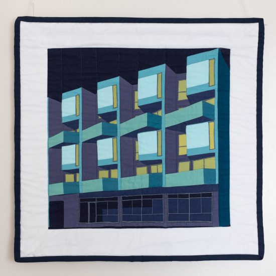 A figurative quilt showing a geometric apartment block in blues and greens.