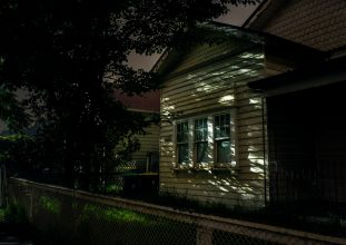 A shadowed weatherboard house photographed at night.