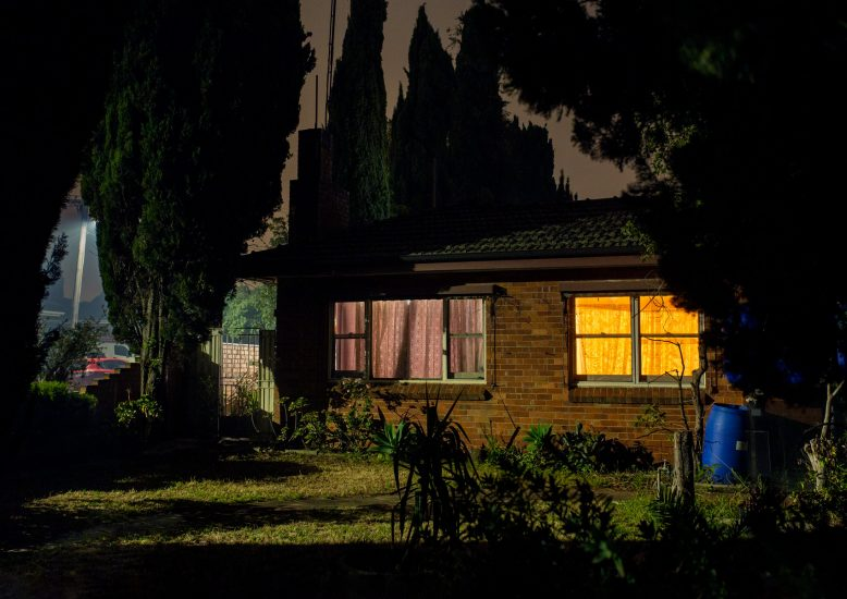 A suburban house photographed at night with dark shadows and two different coloured windows.