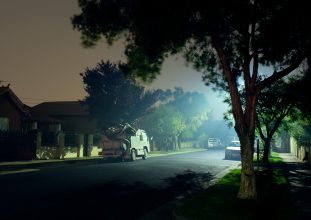 A misty street with a truck lit by a street light.