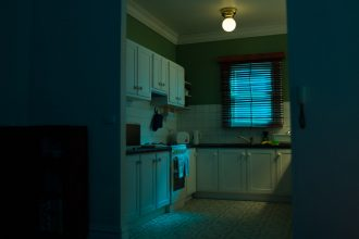 A scale model of a suburban kitchen photographed with blue and green light